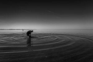 Alter Man im Meer beim Krabbenfischen mit dem Schlepnetz